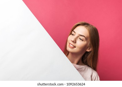 Beautiful young girl peeking out from behind white paper wall, on rose background, isolated