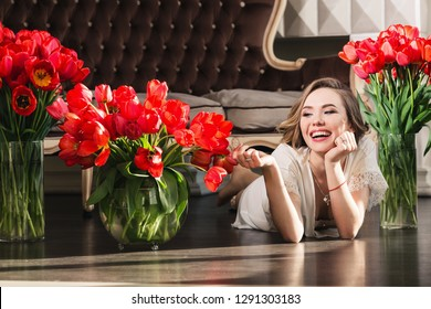 A beautiful young girl in a peignoir is lying on the floor in the studio with bouquets of tulips. The concept of March 8. Morning of the bride