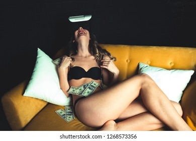Beautiful young girl with a perfect body with a VR headset is lying with a bundle of dollar bills. Naked lady in expensive lingerie. Concept of mindless spending money online stores