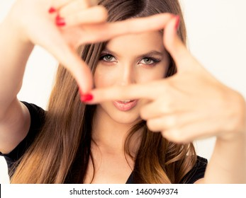 beautiful young girl with perfect skin of the face smiling looks into the camera. close-up portrait with a frame of fingers. positive and emotions