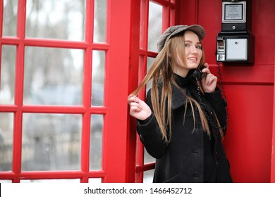 Beautiful young girl in a phone booth. The girl is talking on the phone from the payphone. English telephone booth in the street and a woman talking on the phone.