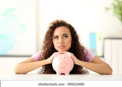Beautiful young girl with piggy bank in office