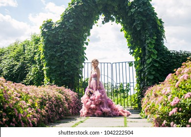 beautiful young girl in a pink dress in a garden.