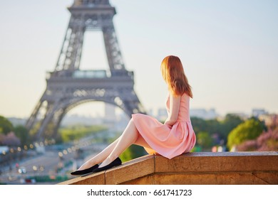 Beautiful young girl in pink dress near the Eiffel tower, enjoying her time in Paris, France