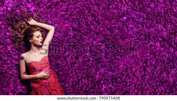Beautiful young girl in pink dress lies on pink petals.