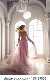 beautiful young girl in pink lace dress spinning in the white room