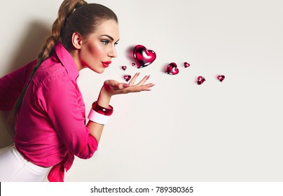 A beautiful young girl in a pink shirt and white skirt stands on a white background and blows from the palm of the heart.