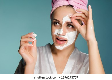 beautiful young girl with a pink towel on her head applies a white cleansing mask on her face