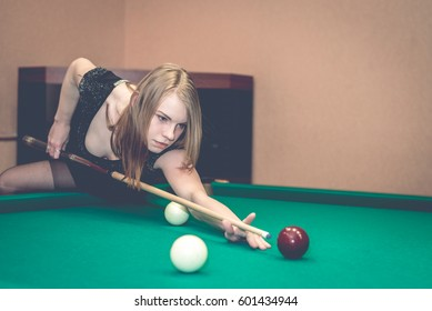 Beautiful young girl playing billiards, sexy woman in billiard room