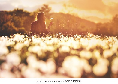 Beautiful young girl playing in dandelion field in beautiful spring warm sunset - filter effect .  Wallpaper full of joy and happiness