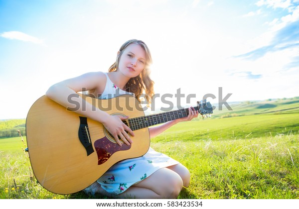 Beautiful young girl playing guitar in the field. Lens flare, selective focus, toned image.