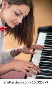 Beautiful young girl playing piano