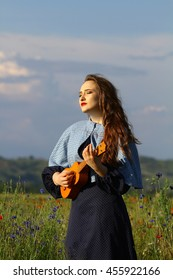 Beautiful young girl playing Ukulele in a flower field in summertime