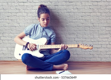 Beautiful young girl plays guitar and composes music on a background of a brick wall.