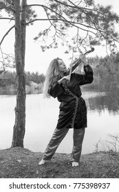 A beautiful young girl plays the violin on the shore of the lake barefoot in early spring. Black and white.