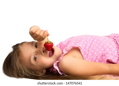 Beautiful young girl in polka dot dress lying down while holding a strawberry next to her open mouth, isolated