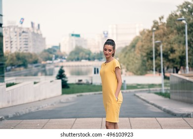 Beautiful young girl portrait dressed in a astonishing yellow dress with a soft focus urban cityscape background feeling great