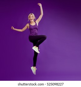 Beautiful young girl in a pose runner. Studio background, purple. Happy jumping