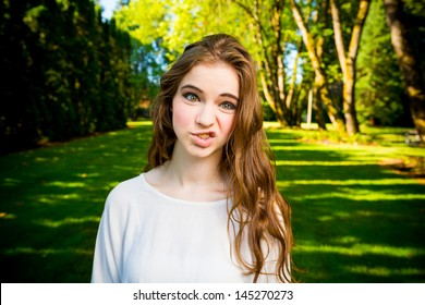A beautiful young girl poses for a fashion style portrait outdoors at a park with natural lighting. - Shutterstock ID 145270273