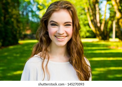 A beautiful young girl poses for a fashion style portrait outdoors at a park with natural lighting. - Shutterstock ID 145270393