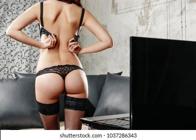 Beautiful, young girl posing in front of a web camera, working as a model. He takes off his bra. The concept of online flirting, sex on the Internet.