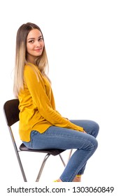 Beautiful young girl posing on a chair over white background.