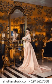 A beautiful young girl in a powdery wedding dress on the background of the interiors of a luxurious historical apartment. An elegant and stylish bride's morning.