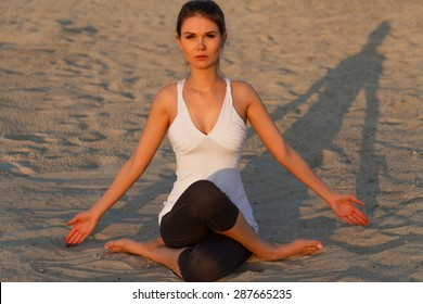 Beautiful young girl practicing yoga on the beach