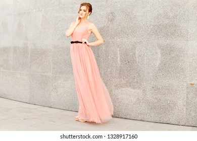 Beautiful young girl at the prom with gorgeous hair in pink dress. Professional make-up and hairstyle , stylish woman .