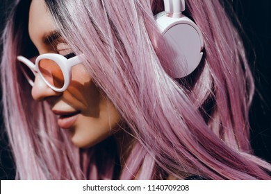 Beautiful young girl with purple pink hair listening to music on headphones, street style, outdoor portrait, hipster girl, music, mp3, Bali, beauty woman, sunglasses, orange color, concept
