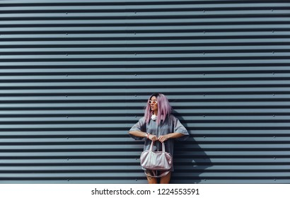 Beautiful young girl with purple pink hair listening to music on headphones, street style, outdoor portrait, hipster girl, music, mp3, Bali, beauty woman, sunglasses, orange color, concept, shopping