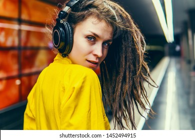 Beautiful young girl with purple pink hair listening to music on headphones, street style, outdoor portrait, hipster girl, music, mp3, Bali, beauty woman, sunglasses, orange color, concept,underground