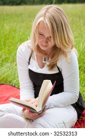 Beautiful young girl reading a book outdoors in the field
