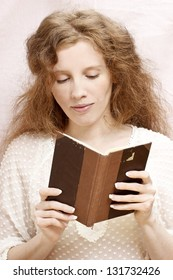 Beautiful young girl reading old book. Pretty face with no make up, long hair, slim hands with perfect french manicure.