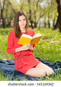 beautiful young girl reads book in park