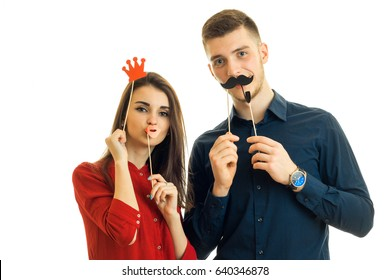 beautiful young girl in a red blouse stands with a guy and they are holding toy mustache, Crown and sponges for photo