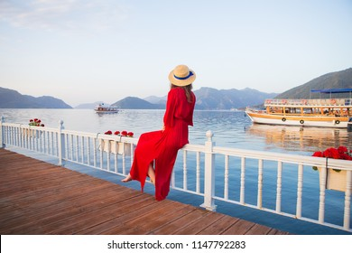 Beautiful young girl in a red dress and a straw hat sits barefoot on a wooden platform. Beautiful views of Marmaris, Turkey