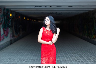 Beautiful young girl in a red dress against the background of a city underground crossing..