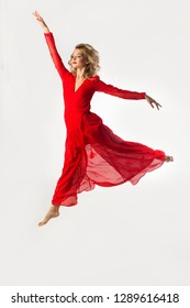 beautiful young girl in a red dress jumping in a ballet pose on a white background