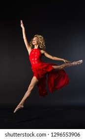 beautiful young girl in red dress jumping in ballet pose on black background