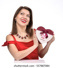 Beautiful young girl in a red dress with a gift in the form of heart. Photo on a white background.