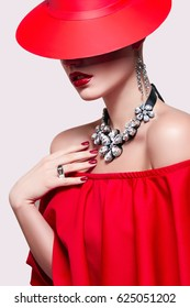 A beautiful young girl in a red dress and a red hat on a white background in the studio. Luxury jewelry, necklaces and rings, bright makeup, red lips, manicure. Glamorous luxury lady.