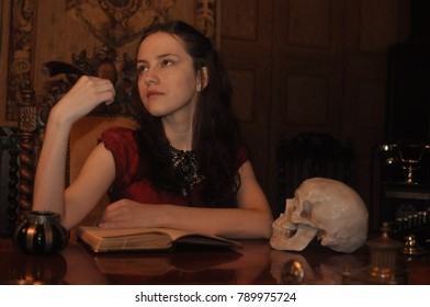 Beautiful young girl in a red dress with a book and a skull on a table on the background of a carpet in St. Petersburg October 16, 2016