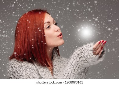 Beautiful young girl with red hair and red nails holding her hands together and blowing on white lightening ball. Pretty woman in grey sweater catching star and making wishes when snowing.