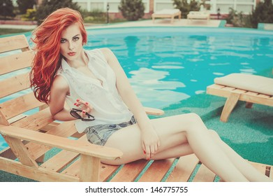 beautiful young girl with red hair lying on a sun lounger