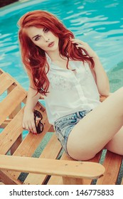 beautiful young girl with red hair lying on a sunbed near the swimming pool