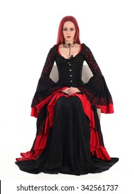 Beautiful young girl with red hair, wearing a long  gothic black and red flamenco lace gown with black corset. sitting on a chair isolated on white background.