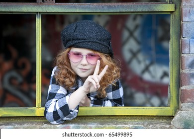 Beautiful young girl with red hair and peace sign  in window of graffiti covered shack