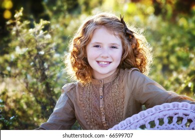Beautiful young girl with red hair outdoors in Autumn season sitting in wicker chair with setting sun behind