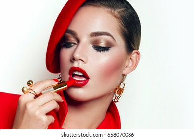 Beautiful young girl in red hat and red jacket. Gold jewelry - earrings, a ring, costume jewelery. Bright make-up - cosmetics for the face. Advertising clothes. He stains his lips with lipstick.
